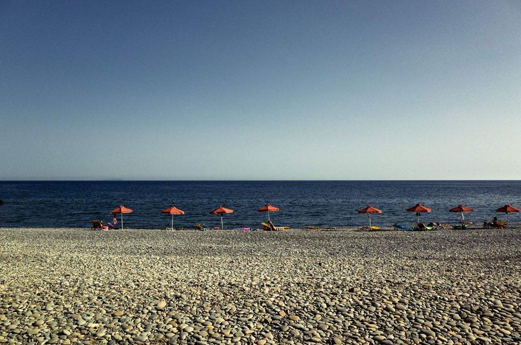 Stony beach and orange umbrellas